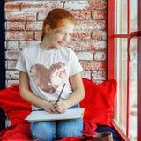 El niño feliz es un adolescente que se sienta en un travesaño y un dibujo de la ventana Foto de archivo