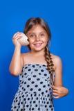 El niño feliz escucha la concha marina Vacaciones de verano y concepto del viaje Fotos de archivo