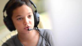 El niño feliz escucha música y jugando en el ordenador con los auriculares al aire libre metrajes