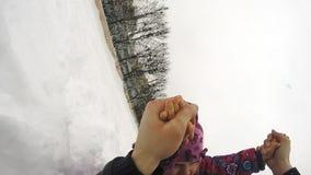 El niño feliz gira y caída en la nieve almacen de video