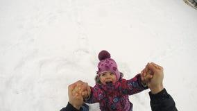El niño feliz gira y caída en la nieve, cámara lenta almacen de metraje de vídeo