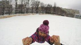 El niño feliz gira y caída en la nieve, cámara lenta almacen de video