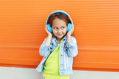 El niño feliz goza escucha la música en auriculares Fotografía de archivo
