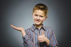 El niño feliz guarda algo a mano y mostrando los pulgares para arriba Imagen de archivo