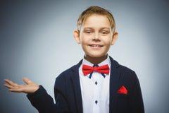 El niño feliz guarda algo a mano y mostrando los pulgares para arriba Imagenes de archivo
