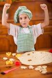 El niño feliz hace las galletas en la cocina imagen de archivo libre de regalías