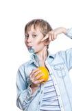 El niño feliz hermoso en camisa elegante bebe el jugo de una naranja con una paja Imagen de archivo