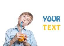 El niño feliz hermoso en camisa elegante bebe el jugo de una naranja con una paja Imagen de archivo libre de regalías