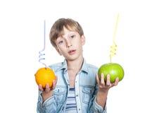 El niño feliz hermoso en camisa elegante sostiene una naranja y un sweety con la paja Fotos de archivo
