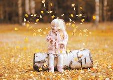 El niño feliz lanza para arriba las hojas amarillas y la diversión el tener en otoño Imagenes de archivo