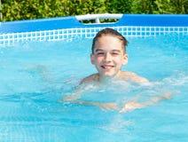 El niño feliz nada en una piscina al aire libre Foto de archivo