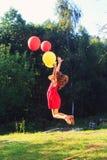 El niño feliz que salta con el juguete colorido hincha al aire libre Sonrisa Foto de archivo libre de regalías