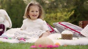 El niño feliz se sienta en un prado alrededor de la decoración de pascua metrajes