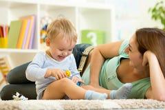 El niño feliz sostiene el juguete animal que juega con la mamá adentro Fotos de archivo