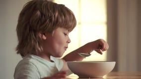 El niño feliz tiene una comida y una bebida de desayuno para los niños Ni?o lindo que come el desayuno en casa Ni?o peque?o que d almacen de metraje de vídeo