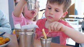 El niño femenino da la salsa para las patatas fritas, muchacho del niño masculino y la muchacha está cenando apetitoso en restaur metrajes