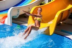 El niño femenino en el tobogán acuático en el aquapark da para arriba Imagen de archivo