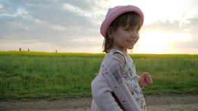 El niño femenino en retrato del contraluz, muchacha sonriente de Runningl, corre a lo largo del camino del campo, niño feliz que  almacen de metraje de vídeo