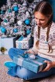 El niño femenino que sostenía el regalo de Navidad en manos cerca adornó el árbol de navidad y la chimenea del abeto Fotografía de archivo