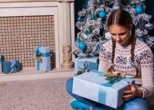 El niño femenino que sostenía el regalo de Navidad en manos cerca adornó el árbol de navidad y la chimenea del abeto Foto de archivo