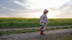 El niño femenino sonriente, niña corre a lo largo del camino del campo, niño corriente, niño feliz que se divierte fuera de la ci metrajes
