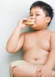 El niño gordo obeso del muchacho come la hamburguesa del pollo Fotos de archivo libres de regalías