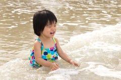 El niño goza de ondas en la playa Fotos de archivo libres de regalías
