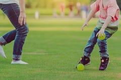 El niño goza a jugar con poca bola en campo foto de archivo
