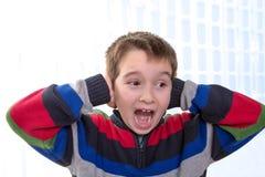 El niño grita con sus manos en sus eras Foto de archivo libre de regalías