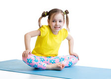 El niño hace la gimnasia que se sienta en actitud de la mariposa Imágenes de archivo libres de regalías
