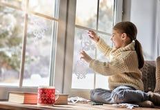 El niño hace los copos de nieve de papel Foto de archivo