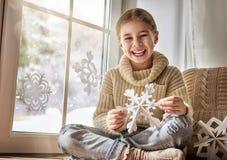 El niño hace los copos de nieve de papel Foto de archivo libre de regalías