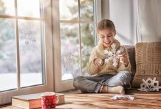 El niño hace los copos de nieve de papel Imágenes de archivo libres de regalías