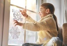 El niño hace los copos de nieve de papel Fotos de archivo libres de regalías