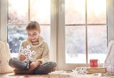 El niño hace los copos de nieve de papel Fotografía de archivo
