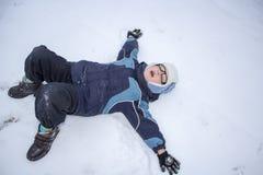 El niño hace un ángel de la nieve Imagenes de archivo