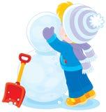 El niño hace un muñeco de nieve Foto de archivo libre de regalías