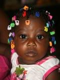 El niño haitiano adornó con los pasadores coloridos en Haití rural Foto de archivo