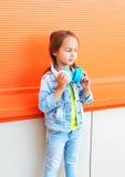 El niño hermoso de la niña que lleva vaqueros viste con los auriculares Imágenes de archivo libres de regalías