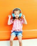 El niño hermoso escucha la música en auriculares sobre fondo anaranjado colorido Imagenes de archivo