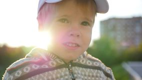 El niño hermoso mira en la cámara y sonríe contra la perspectiva de rayos del sol Diversión al aire libre almacen de metraje de vídeo