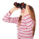El niño hermoso mira a través de los prismáticos Fotos de archivo