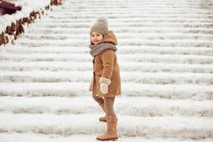 El niño hermoso muy bonito de la muchacha en una capa beige y un sombrero gris van Fotografía de archivo libre de regalías