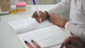 El niño hispánico está haciendo tarea de la matemáticas en el cuaderno para prepararse a la nueva lección en casa metrajes