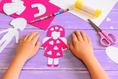 El niño hizo una muñeca del ángel de la cartulina Las manos de los niños en una tabla de madera Las herramientas y los materiales Foto de archivo libre de regalías