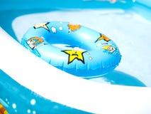 El niño infla la piscina y nada el anillo Fotografía de archivo libre de regalías