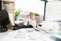 El niño inteligente alegre se está sentando en oficina Fotografía de archivo
