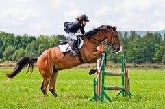 el niño-jinete con el caballo salta sobre un cañizo Imágenes de archivo libres de regalías