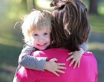 El niño joven lindo abraza a su mamá fotografía de archivo libre de regalías