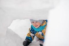 El niño joven lindo del muchacho está jugando afuera en túnel del fuerte del iglú que él cavó en la pila de nieve el día de invie Fotos de archivo libres de regalías